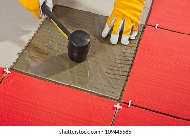 Worker with rubber hammer install glass tiles with tile adhesive.