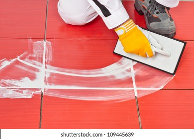 worker with rubber trowel applying white grout on red tiles on floor