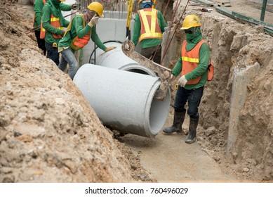 Worker in safety uniform install concrete precast pipe drainage under ground road