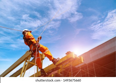 worker safety uniform, Rope access at construction wearing full safety body harness with helmet protection hanging upside on roof factory and crane background.