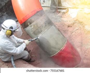 worker sandblasting to rusty pipe
