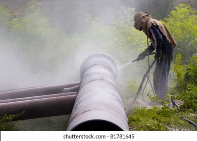 A worker sandblasting the weld during the construction of pipelines