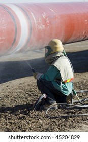 A worker sandblasting the weld in preparation for coating during pipeline construction