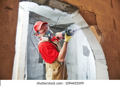 Worker sawing doorway with sabre saw. Home renovation
