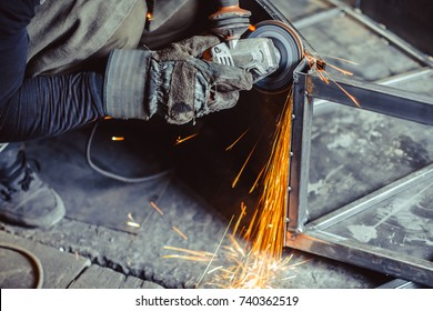 worker sawing metal with a saw, sparks fly