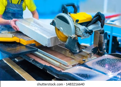 Worker sawing stone slab. Circular saw. Stone and tile cutting equipment. The shop is equipped with a circular saw. Ceramic tile and stone cutting machine. Processing of stone and tile.