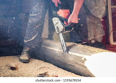 the worker saws off a log with a chainsaw