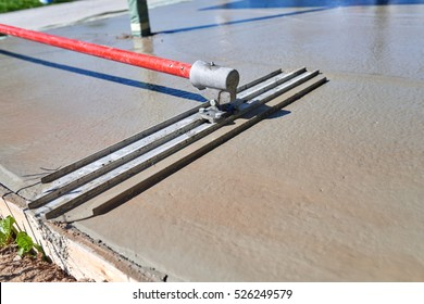 Worker screeding cement floor with bull float Leveling concrete with bull float, mason hands spreading poured concrete