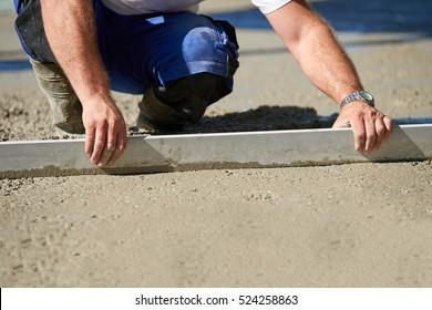 Worker screeding cement floor with screed