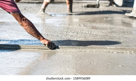 Worker screeding cement on the floor using a screed outdoor.