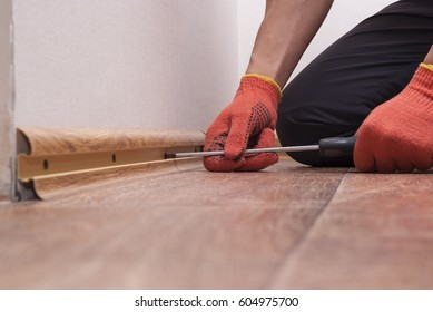 worker with a screwdriver in his hands mounts a floor plinth