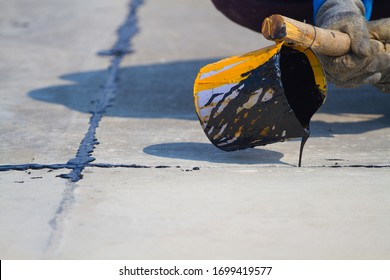 Worker sealing asphaltic joint for construction joint on concrete pavement, filling expansion joint concrete pavement.