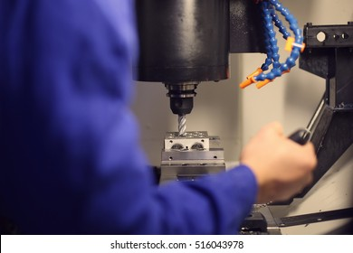 Worker securing a detail in a vise on CNC machine