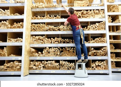 worker or seller in construction store or warehouse wood section at work