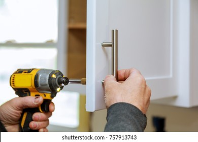 The worker sets a new handle on the white cabinet with a screwdriver installing kitchen cabinets