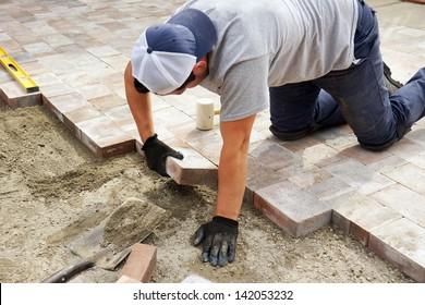 Worker setting paver bricks on large patio, paving backyard