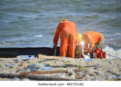 Worker setup equipment for clean spill oil at  beach and blurred foreground of plastic bottles ,other trash.