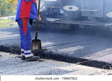 Worker with shovel to begin to the asphalt cover
