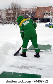 worker with a shovel clears snow in winter