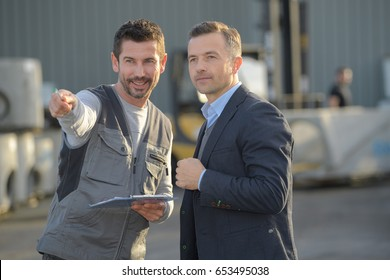 worker showing something to manager in industry