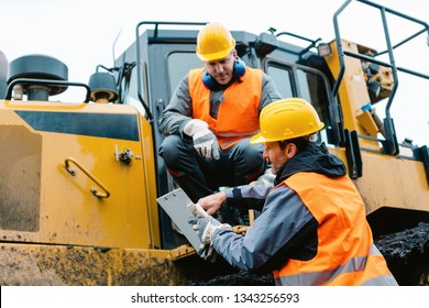 Worker sitting on heavy excavation machinery in mining operation