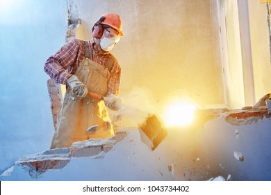 worker with sledgehammer at indoor wall destroying