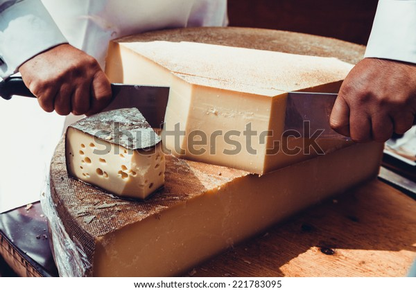 Worker slicing the cheese. Close up of Cutting cheese.