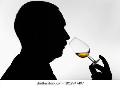 Worker smelling whisky in distillery