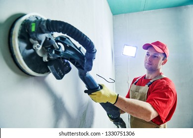 Worker smoothig and finishing wall with long reach sander before painting