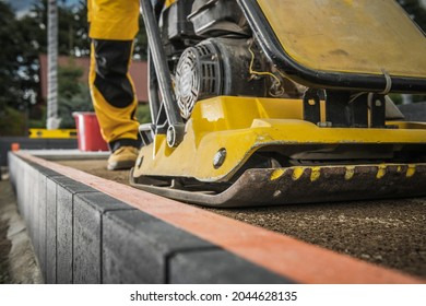 Worker with Soil Compactor Preparing Ground For Paving. Heavy Duty Construction Machinery.
