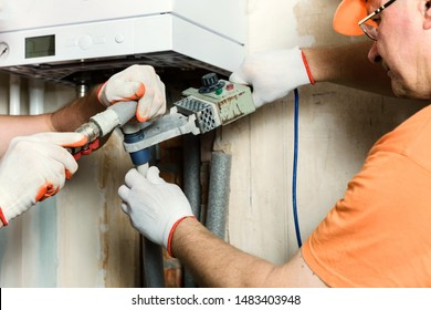 The worker is soldering plastic pipes and connecting them to a domestic gas boiler.