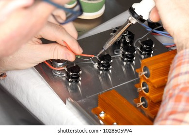 worker is soldering a wire on an electrical device