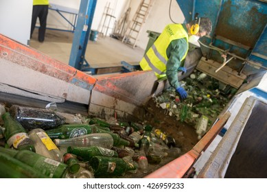 Worker is sorting the recyclable glass material and removing non recyclable things on a conveyor belt during recycling process, recycling factory EKOPAK, Verila, Bulgaria, May 26, 2016.