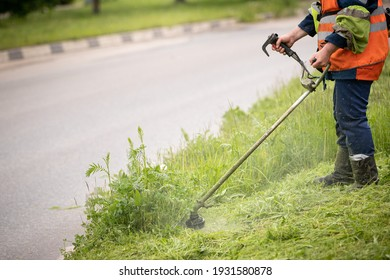 A worker in special reflective clothing with a gasoline mower in his hand. A man with a trimmer mows grass with dandelions on the side of the road