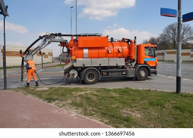 Worker and specialist car. Cleaning sewer manholes.