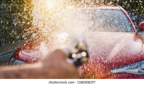 Worker Spraying foam to a red sports car with high pressure foam gun car wash at car wash