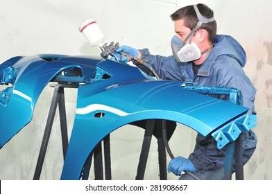 Worker spraying gray base coat.