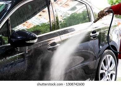 Worker spraying misty water onto car to wash at garage