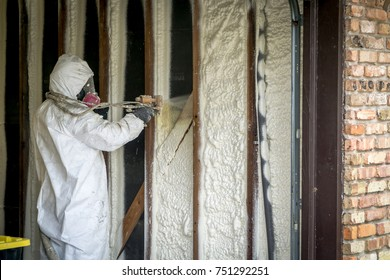 Worker spraying open cell spray foam on the wall of a home flooded by Hurricane Harvey