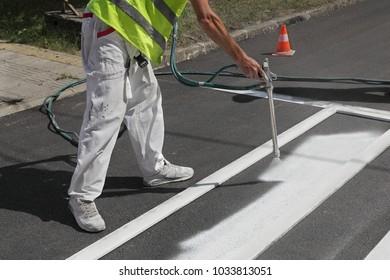 Worker spraying pedestrian crosswalk at a street,  repairing and painting