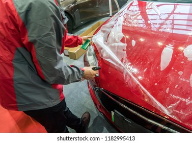 Worker spraying water onto car to install paint protection film