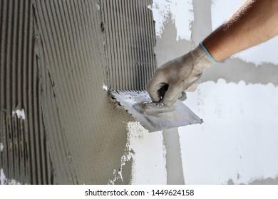 Worker spreading  mortar over styrofoam, polystyrene insulation using trowel
