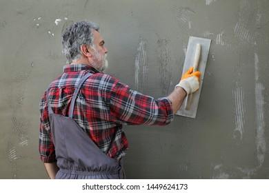 Worker spreading  mortar over styrofoam, polystyrene insulation and netting using trowel