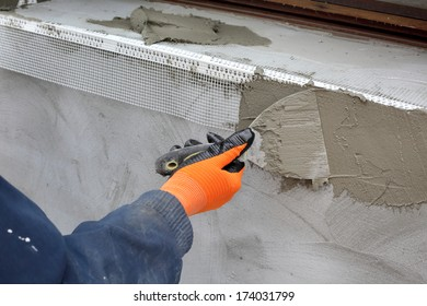 Worker spreading  mortar over styrofoam insulation with trowel