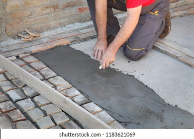 Worker spreading mortar or tile adhesive using trowel, old tiles recycling, making terrace or pavement using tile pieces