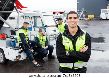 Worker Standing Arms Crossed While Colleagues Communicating At G