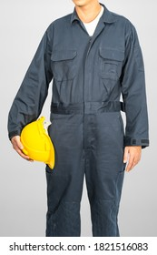 Worker standing in blue coverall holding yellow hardhat isolated on gray background