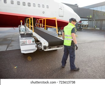 Worker Standing By Luggage Conveyor Attached To Airplane