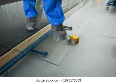 The worker is standing on a pane of thick glass. Durable, thick tempered glass