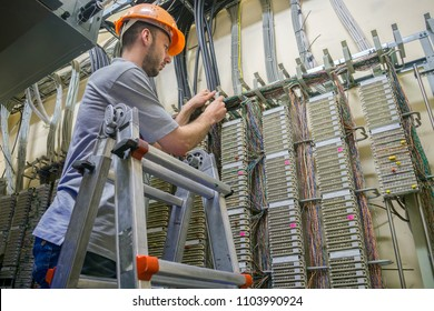 A worker standing on the stairs commutes telephone wires. The engineer works in the server room of the data center. Cable laying in telephone exchange
